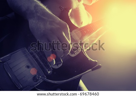 man playing electrical guitar in black and yellow #69678460