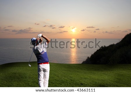 man playing golf  against sunset over sea
