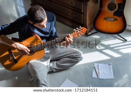 Man playing guitar and composing music at home near a bright window on a sunny day. Casual musician sitting on the floor playing the guitar. Foto stock ©