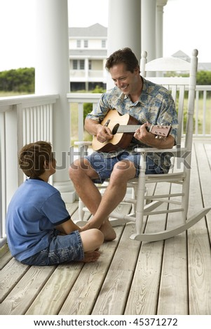 Man playing guitar as a boy listens on the front porch of his home. Vertical shot.