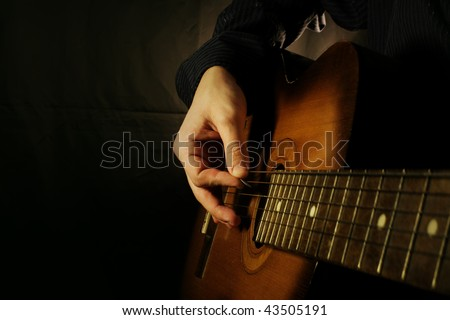 man playing guitar at black background
