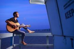 Man playing guitar at dusk beach
