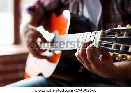 Man playing guitar. Close-up of man playing acoustic guitar while sitting in front of the window