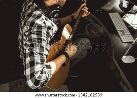 Man playing guitar in a recording studio. Concept guitarist composing songs and music #1342182539