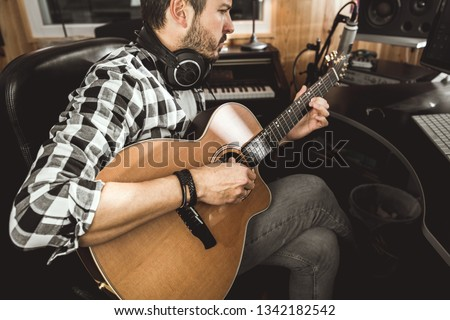 Man playing guitar in a recording studio. Concept guitarist composing songs and music #1342182542
