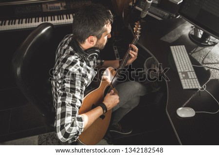 Man playing guitar in a recording studio. Concept guitarist composing songs and music #1342182548