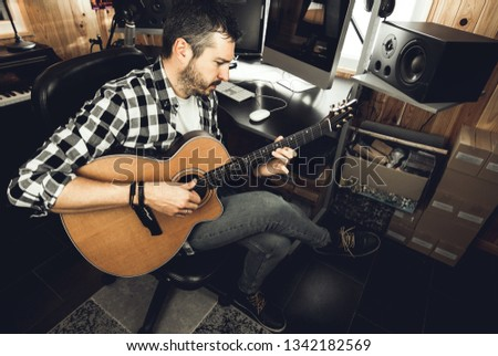 Man playing guitar in a recording studio. Concept guitarist composing songs and music #1342182569