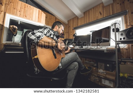 Man playing guitar in a recording studio. Concept guitarist composing songs and music #1342182581