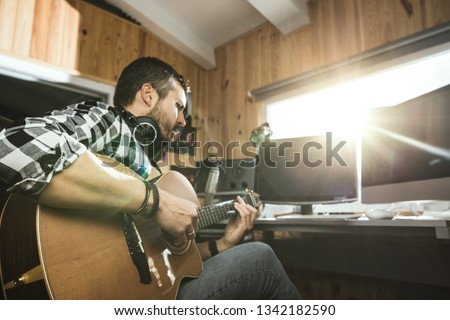 Man playing guitar in a recording studio. Concept guitarist composing songs and music #1342182590