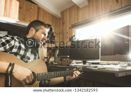 Man playing guitar in a recording studio. Concept guitarist composing songs and music #1342182593