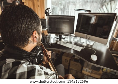 Man playing guitar in a recording studio. Concept guitarist composing songs and music #1342182596