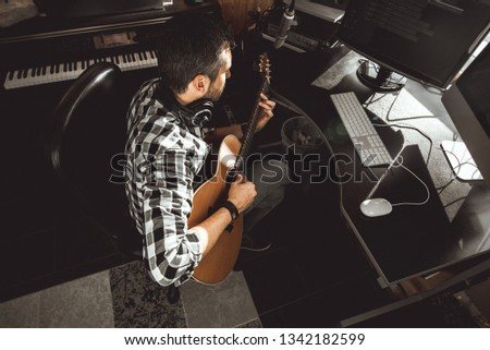 Man playing guitar in a recording studio. Concept guitarist composing songs and music #1342182599