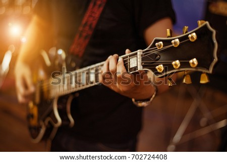 man playing guitar on a stage musical concert close-up view.guitarist plays. #702724408