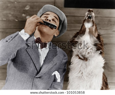Man playing harmonica with howling dog
