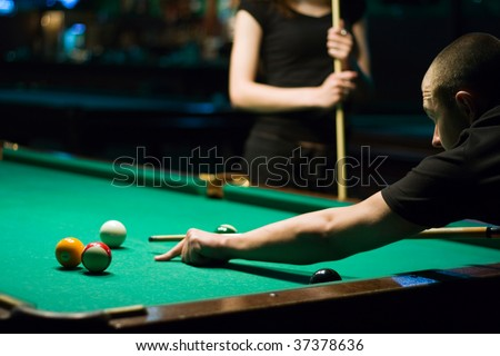 Man playing in billiard in dark billiard room and woman with cue to background