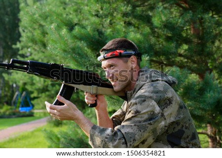 Man playing in lasertag shooting game in open air. Weapon in the hands of people. War simulation.