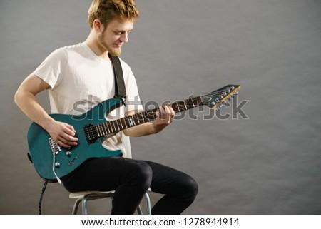 Man playing on electric guitar during gig. Musical instrument. Teenage boy having music hobby. #1278944914