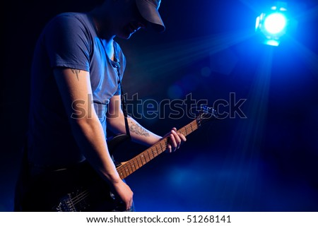 man playing on guitar over blue