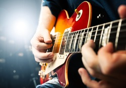 man playing on guitar, stage light, musical concert close up view
