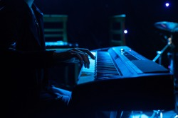Man playing on synthesizer keyboard on stage during concert backlight, colors intentionally altered