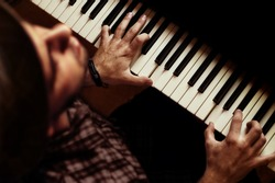 Man playing piano on dramatic dark stage