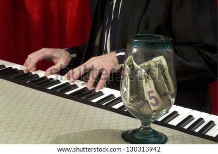 man playing piano with tips jar on piano