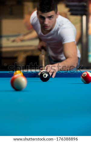 Man Playing Pool - Lining To Hit Ball On Pool Table