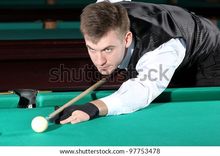 Man playing snooker in the dark club.