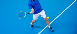 man playing tennis on blue floor