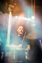 Man playing the drums of a musical group