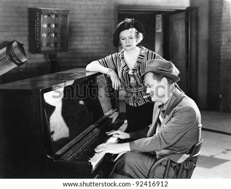 Man playing the piano while a woman is listening - stock photo