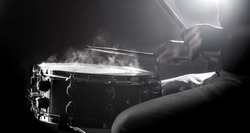 man playing the snare drum on a beautiful colored background, the concept of musical instruments