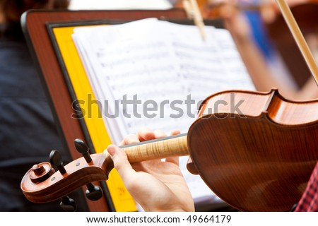man playing the violin with a musical score in the background