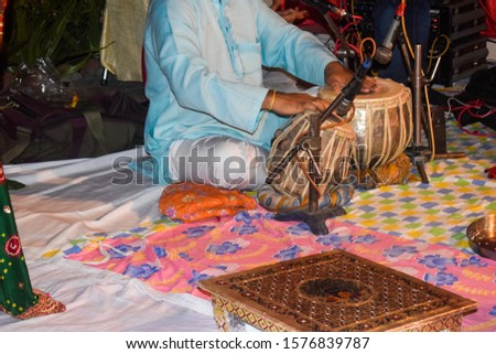 Man playing traditional Indian instrument Tabla