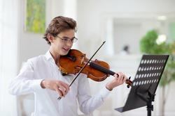 Man playing violin. Classical music instrument. Teenage boy practicing viola. Teenager art school student.