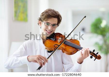 Man playing violin. Classical music instrument. Teenage boy practicing viola. Teenager art school student. Сток-фото ©