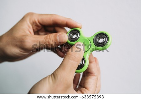 Man playing with a green hand spinner fidget toy