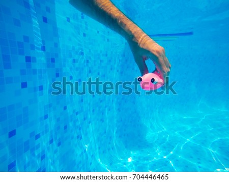 Man playing with generic rubber fish toy in swimming pool, summertime activity and enjoyment, underwater shot #704446465