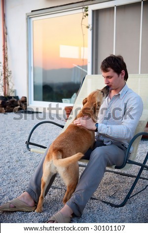 man playing with his dog in front of the house