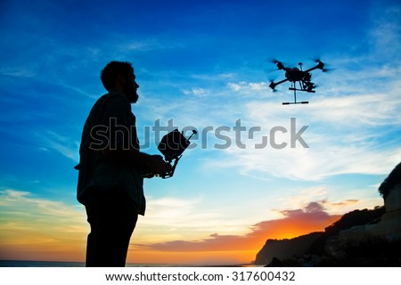 Shutterstock man playing with the drone. silhouette against the sunset sky