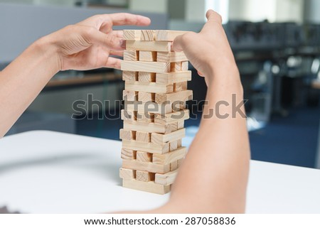 Man playing with the wood game (jenga) in the office