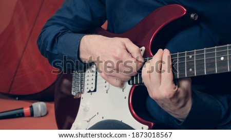 Man plays a guitar in the background you can see a microphone and a second guitar Stockfoto ©