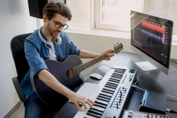 Man plays guitar and produce electronic soundtrack or track in project at home. Male music arranger composing song on midi piano and audio equipment in digital recording studio.