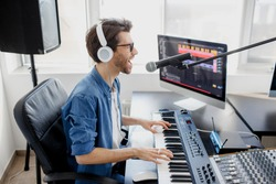 Man plays guitar and singing and produce electronic soundtrack or track in project at home. Male music arranger composing song on midi piano and audio equipment in digital recording studio