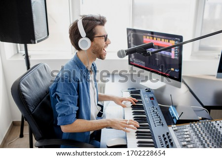 Man plays guitar and singing and produce electronic soundtrack or track in project at home. Male music arranger composing song on midi piano and audio equipment in digital recording studio Foto stock ©