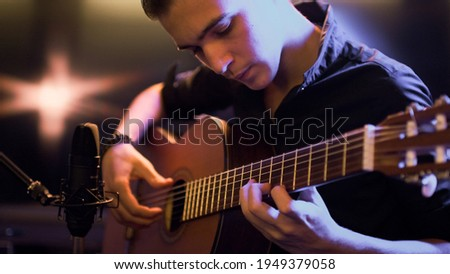 Man plays guitar. Young man plays a musical instrument. Musician records his composition in a music Studio using professional microphone Photo stock ©
