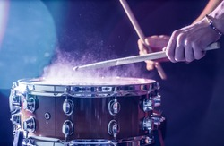 man plays musical percussion instrument with sticks closeup on a black background, a musical concept with the working drum, beautiful lighting on the stage