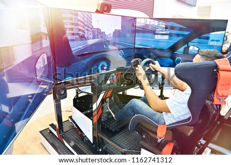 Man plays on a computer racing simulator