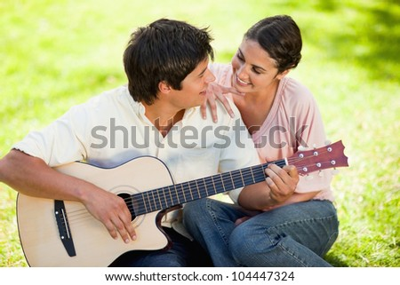 Man plays the guitar while looking at his friend who has her hand on his shoulder as they both sit on the grass