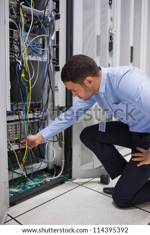 Man plugging a cable into server in data center